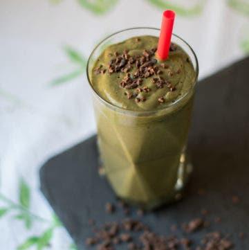 Glas mit grünem Smoothie und rotem Strohhalm, garniert mit Kakaonibs