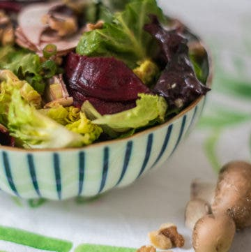 seitliche Ansicht von gestreifter Schüssel gefüllt mit grünem Salat, roter Bete und Champignons