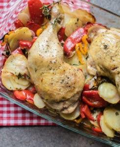 Backofenform aus Glas gefüllt mit Paprika, Kartoffelscheiben und Hähnchenschenkeln