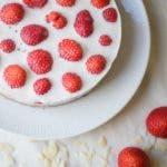 Topshot von rundem Kuuchen mit weißer Panna Cotta und ganzen Erdbeeren