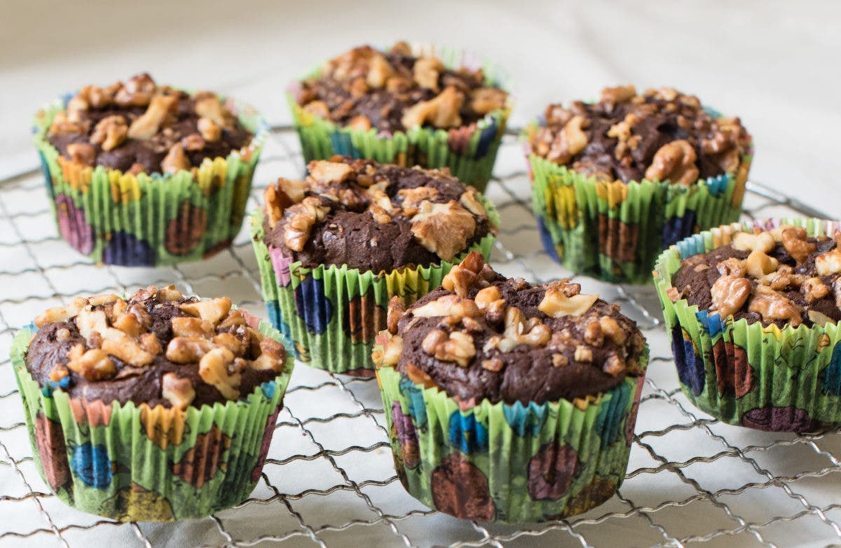 Sieben Schokomuffins in grünem Muffinpapier mit gehackten Walnüssen als Topping