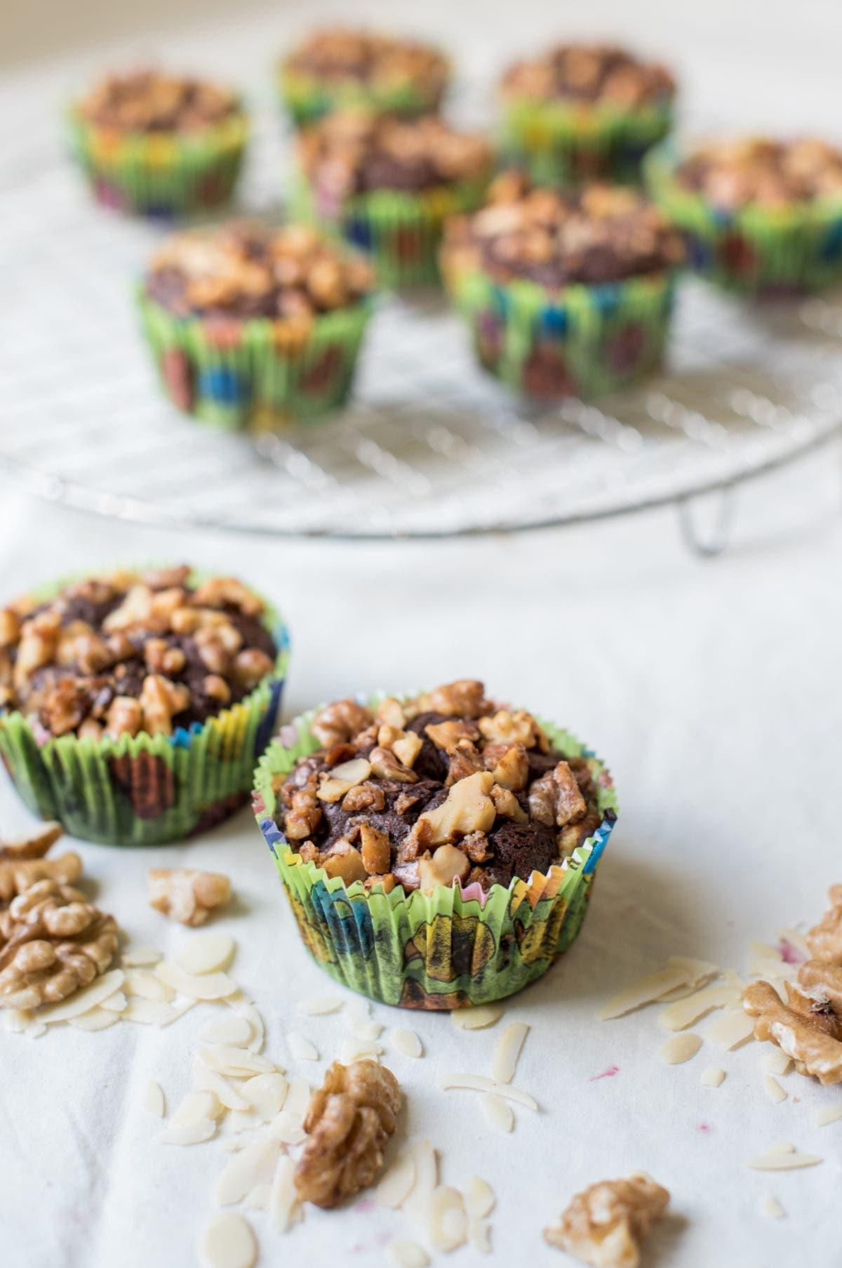 leicht erhöhte Ansicht von zwei Schokomuffins vor Backrost mit weiteren Muffins