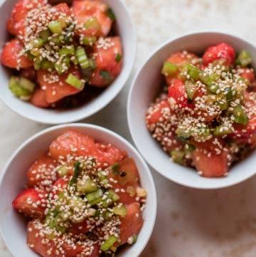 Topshot von drei Schüsseln gefüllt mit Wassermelonensalat und getoppt mit Sesam und Kräutern