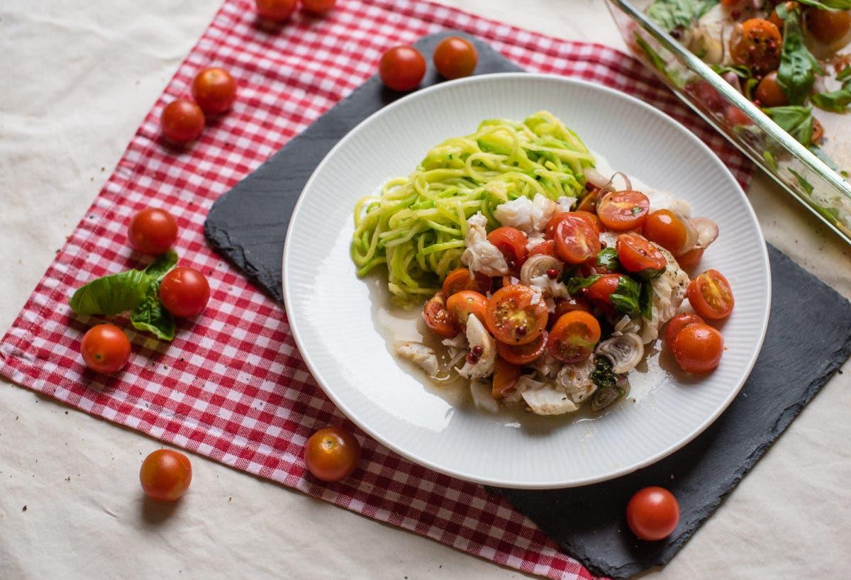Teller mit Kabeljau aus dem Ofen, Zucchininudeln und halbieren Kirschtomaten