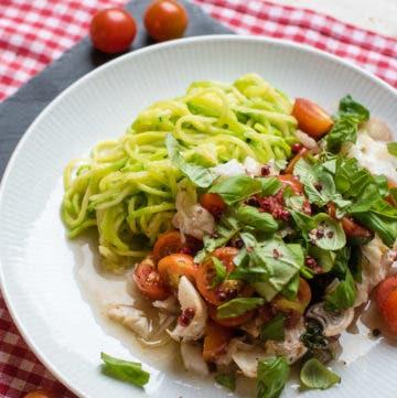 Nahaufnahme von Teller mit Kabeljau, Zucchinipasta und Tomaten aus dem Ofen