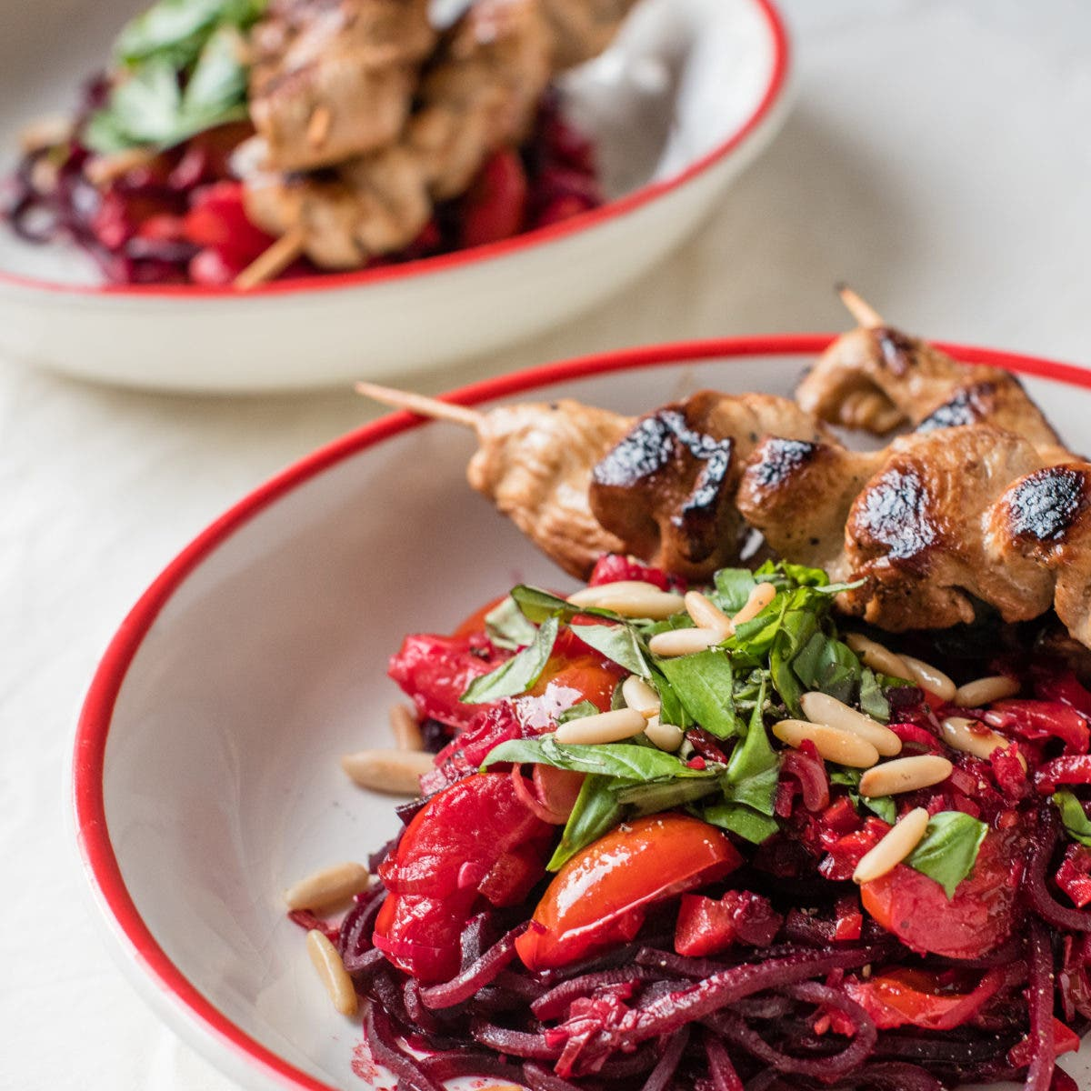 Nahaufnahme von roter Bete Pasta mit Hühnerspießen auf Teller
