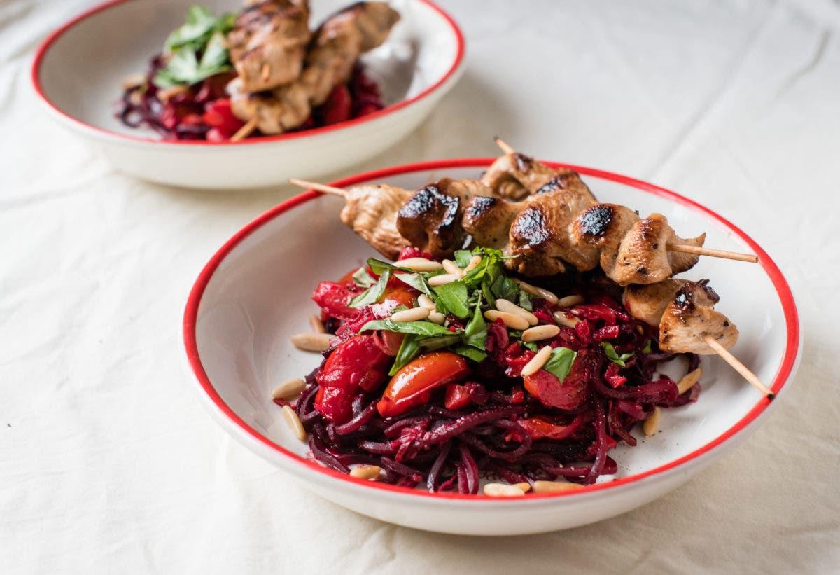 Zwei Teller mit roter Bete Pasta und Hühnerspießen auf weißer Tischdecke