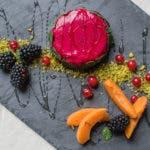 Toptshot von pinkem Panna Cotta mit frischen Früchten auf Schieferplatte