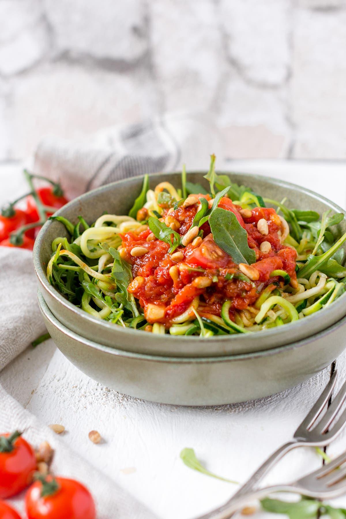 Schüssel gefüllt mit Zucchini Pasta: Nudeln, Rucola und Tomatensauce auf weißem Untergrund.