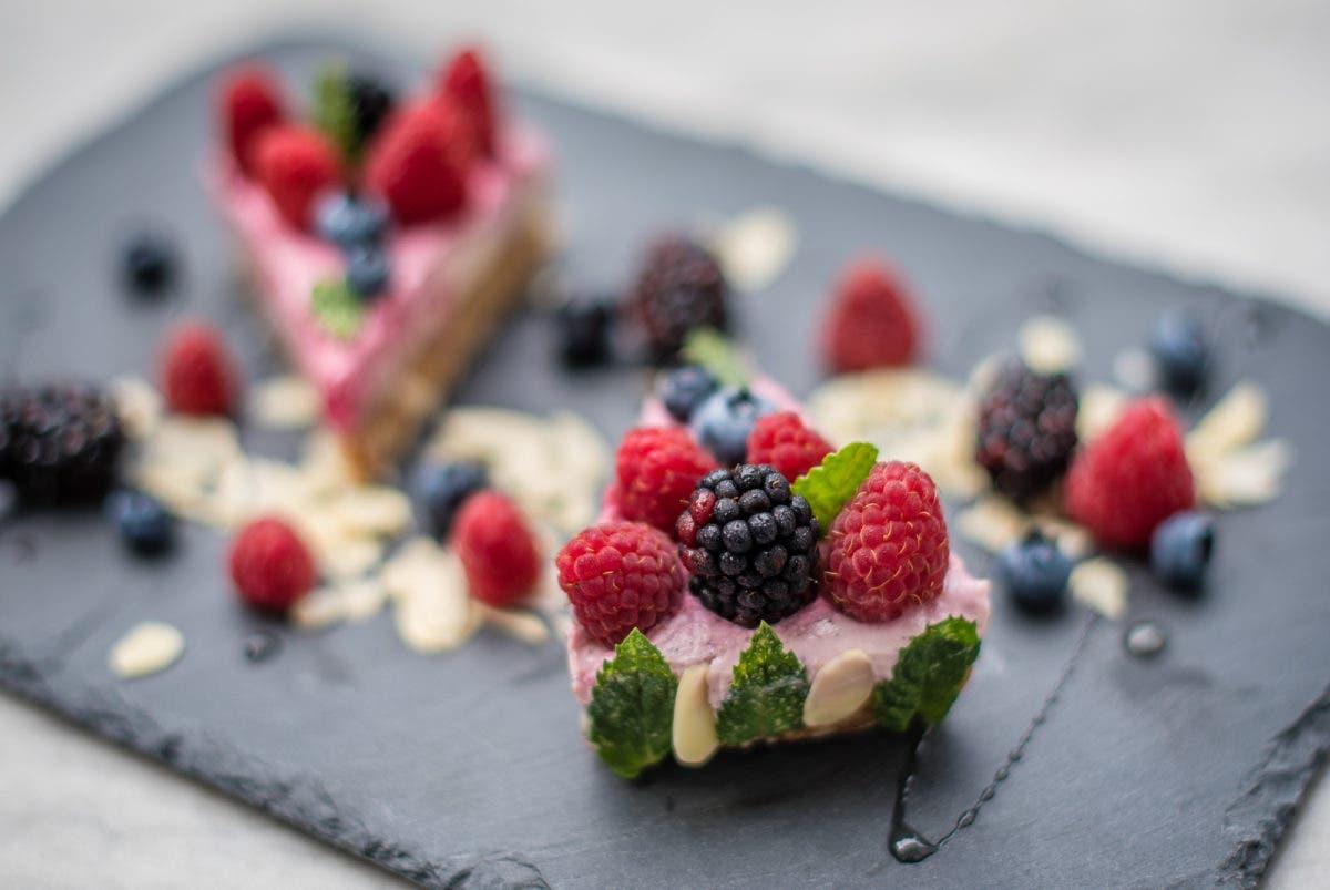 Rückansicht von Kuchenstück mit Minzblättern und bunten Früchten garniert