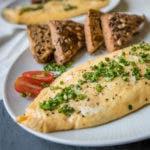Nahaufnahme von Omelette mit Kräutern und Brotscheiben im Hintergrund