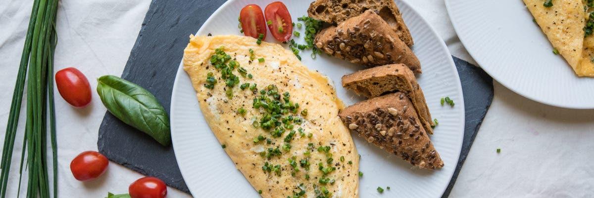 Topshot von Omelette mit Brotscheiben, Kräutern und Tomaten angerichtet
