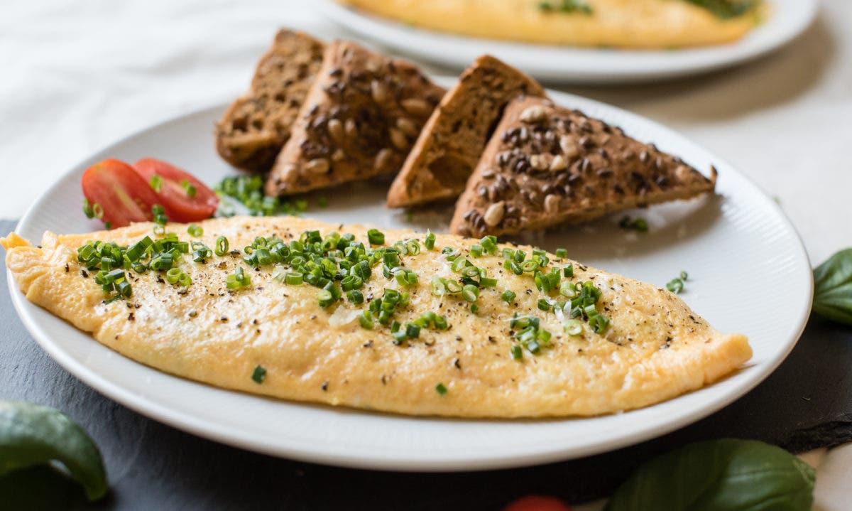 Omelette mit Schnittlauch und Brotscheiben auf Teller