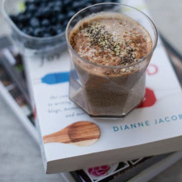 Glas gefüllt mit Iced Chai Latte auf Bücherstapel mit Blaubeeren im Hintergrund