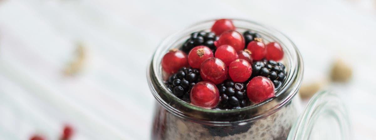 Nahaufnahme von kleinem Glas mit Brombeeren und Johannisbeeren