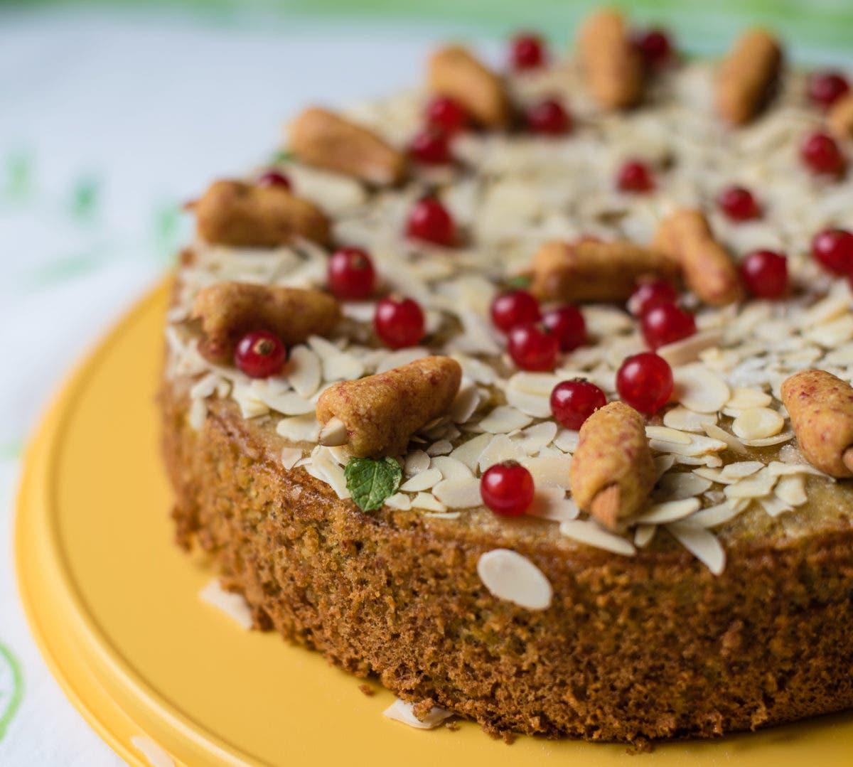 Seitliche Ansicht von Kuchen dekoriert mit Mandeln und Marzipankarotten, auf gelber Kuchenplatte