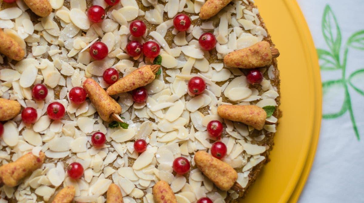 Topshot von Karottenkuchen dekoriert mit Mandelblättchen,Johannisbeeren und Marzipankarotten auf gelber Kuchenplatte