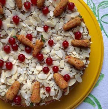 Topshot von rundem Kuchen mit Mandelblättchen,Johannisbeeren und Marzipankarotten auf gelber Kuchenplatte