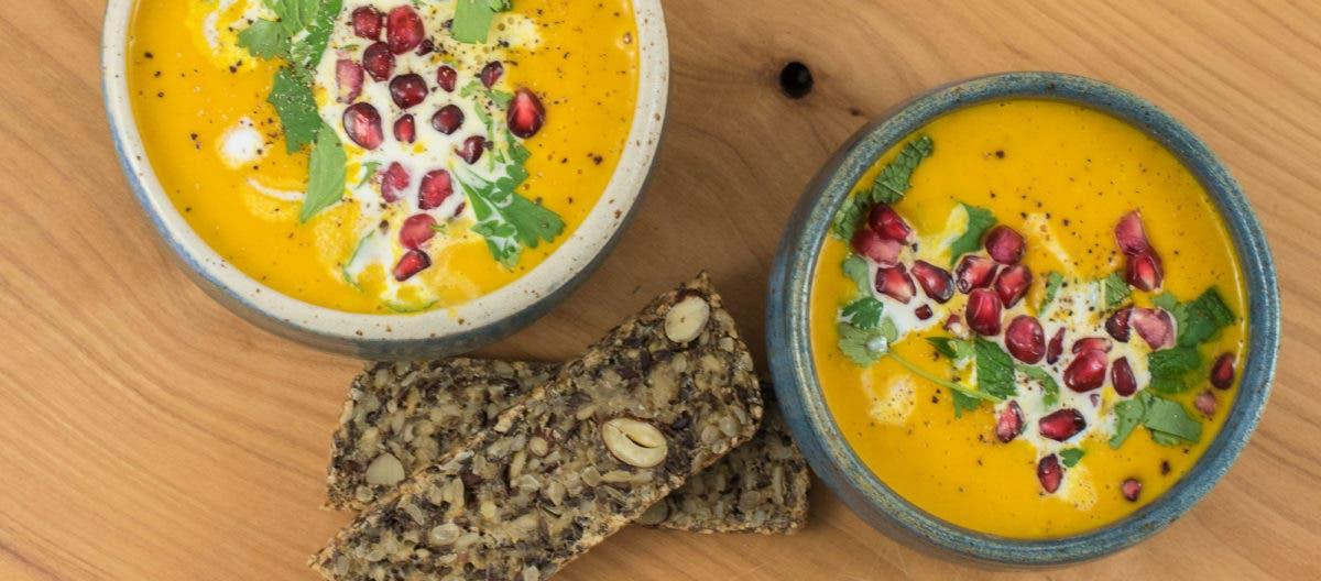 Topshot von zwei Suppenschalen mit gelbem Inhalt, Granatapfelkernen, dazu Körnerbrot