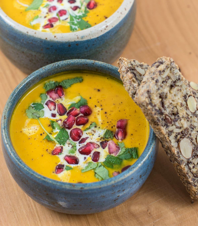 Dunkelblaue Schüssel mit gelber Suppe, garniert mit Granatapfelkernen und Körnerbrot