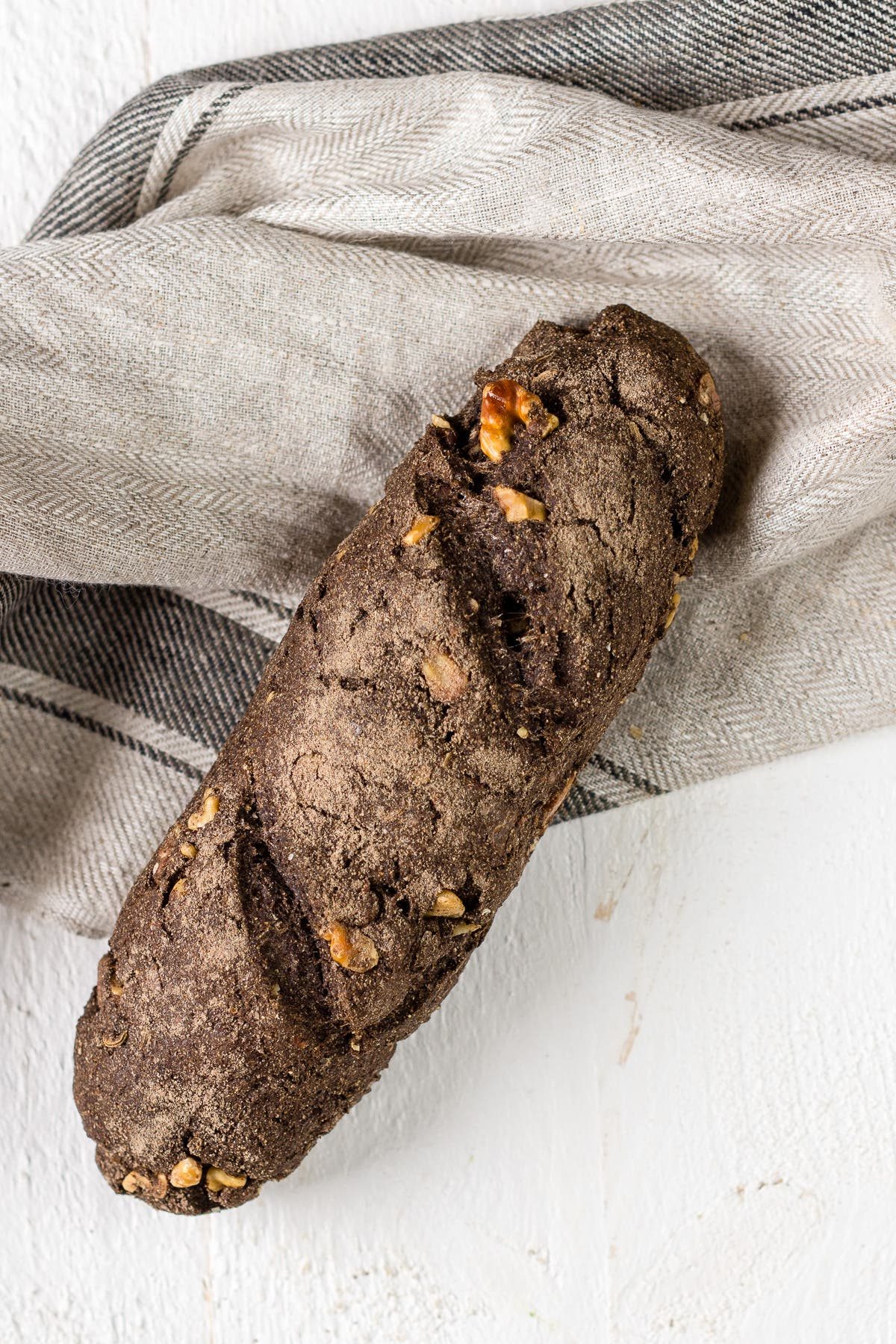 Topshop von Walnussbaguette auf hellem Tuch liegend