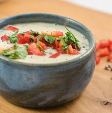 seitliche Nahaufnahme von heller Cremesuppe in Schüssel, garniert mit Paprika und Petersilie