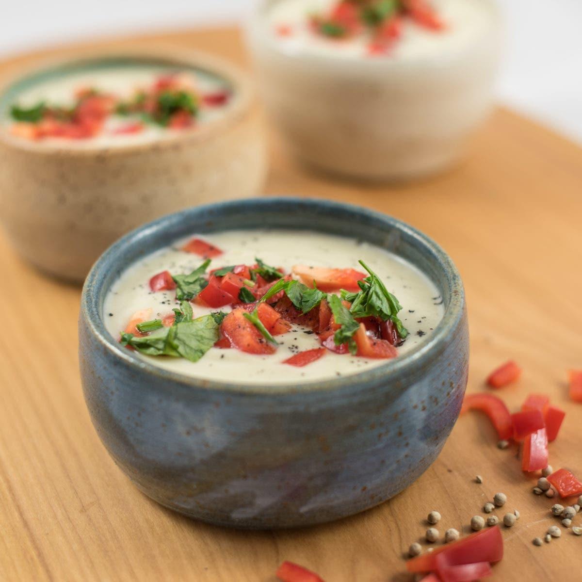 Nahaufnahme von gefüllter Suppenschüssel mit Cremesuppe und garniert mit Petersilie und roter Paprika