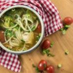 Topshot von klarer Brühe in Suppenschüssel mit Suppeneinlage