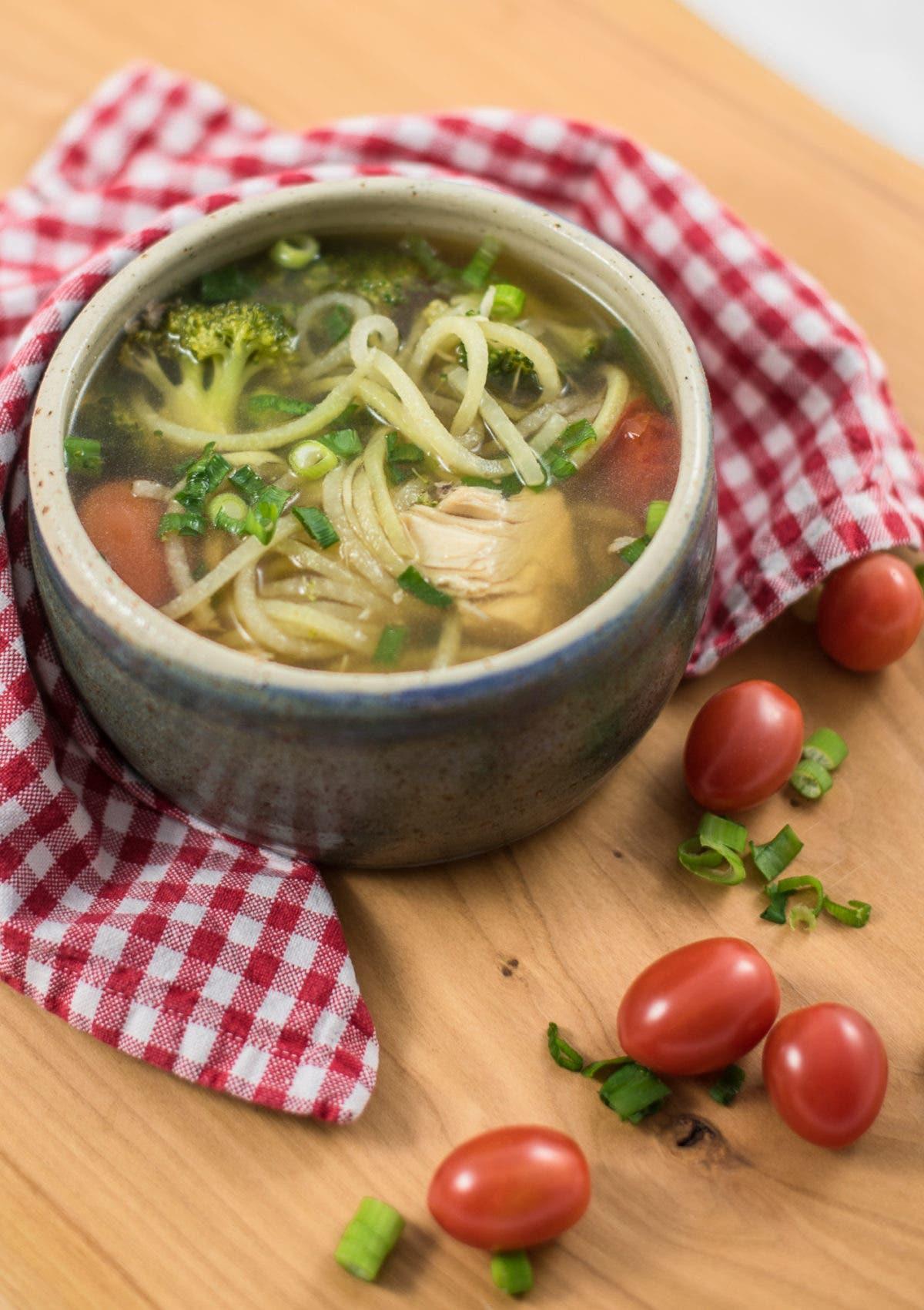 Suppenschüssel mit klarer Brühe und Suppeneinlage auf Holztisch mit rot kariertem Tuch und Tomaten