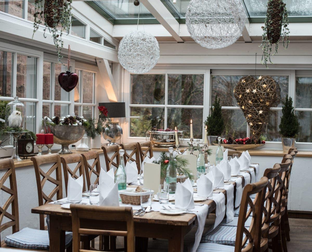 lange, eingedeckte Tischtafel in Restaurant im Odenwald mit weihnachtlicher Dekoration