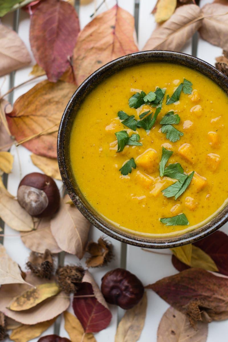 Topshot von gelber Suppe in brauner Schale auf weißem Tisch mit herbstlichen Blättern dekoriert
