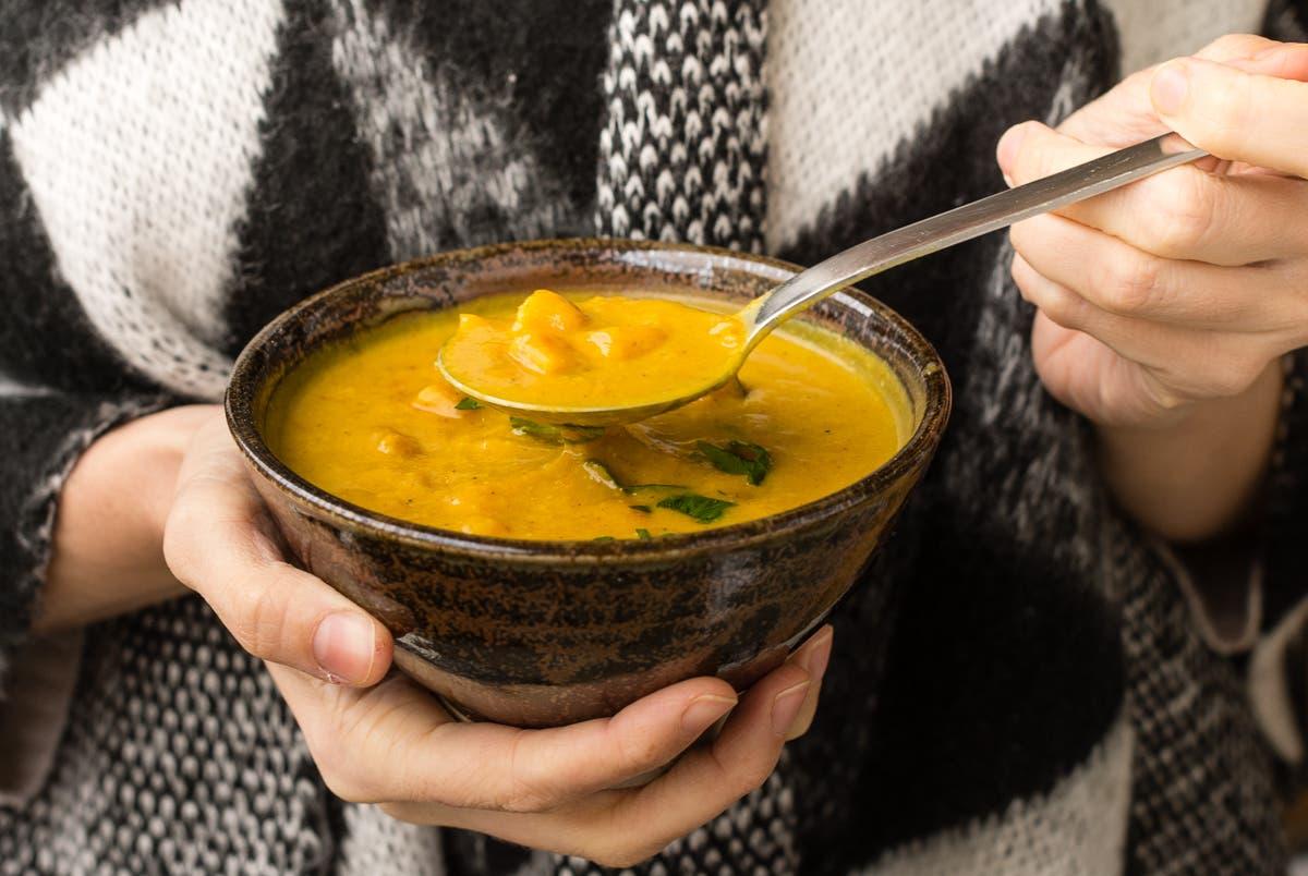 Hände halten braune Schüssel mit gelber Suppe