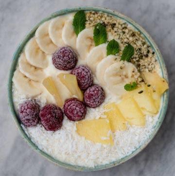 Topshot von Smoothiebowl getoppt mit Himbeeren, Banane, Ananas und Kokosflocken