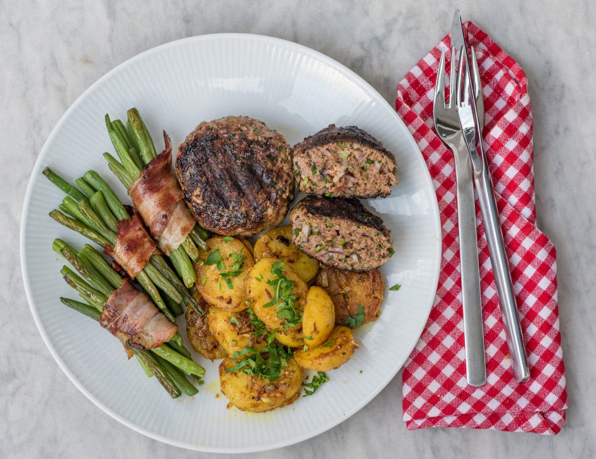 Topshot von Teller mit Frikadellen, Speckbohnen und Kartoffeln und Besteck rechts davon auf Serviette liegend