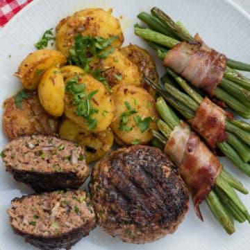 Frikadellen mit Speckbohnen und Kartoffeln auf weißem Teller