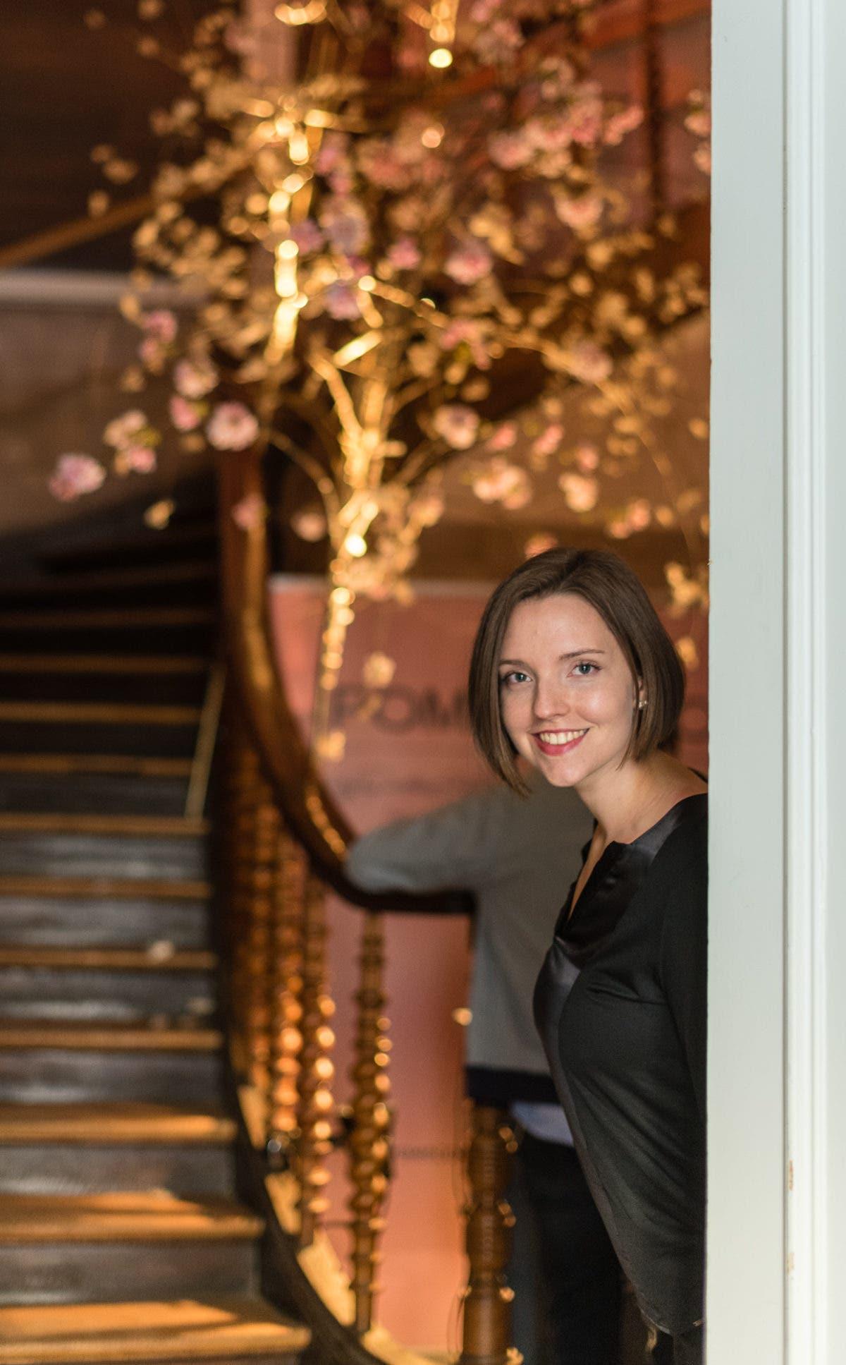 Frau steht vor Treppe und lächelt in die Kamera.