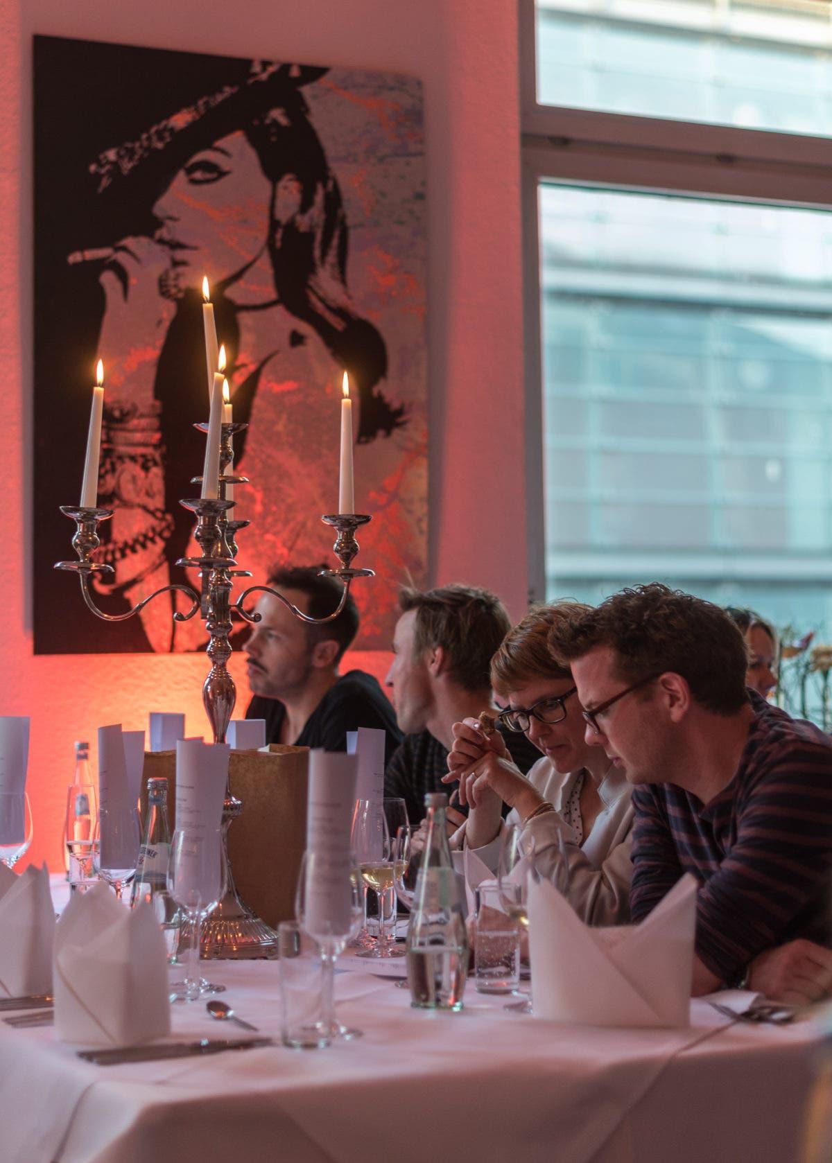 Personen sitzen am gedeckten Tisch mit großem Kerzenständer.