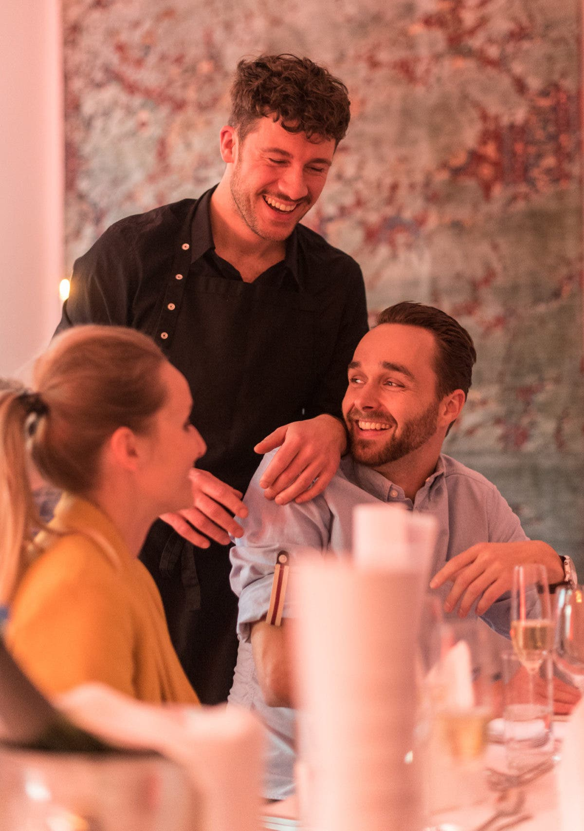 Personen in einem Restaurant lachen und amüsieren sich.