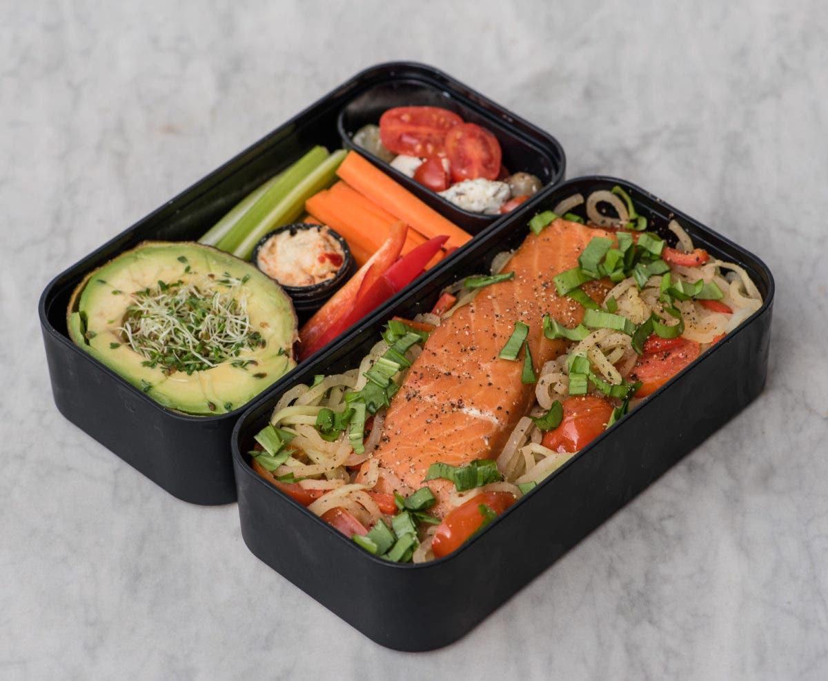 Seitlich erhöhtes Foto von Lunchbox gefüllt mit buntem Gemüse und Lachs