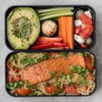 Topshot von Brotdose mit buntem Gemüse und Lachs gefüllt