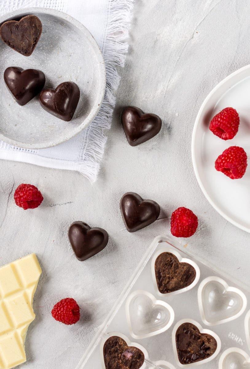 Topshot von Schokoladen Herz Pralinen und frischen Himbeeren.