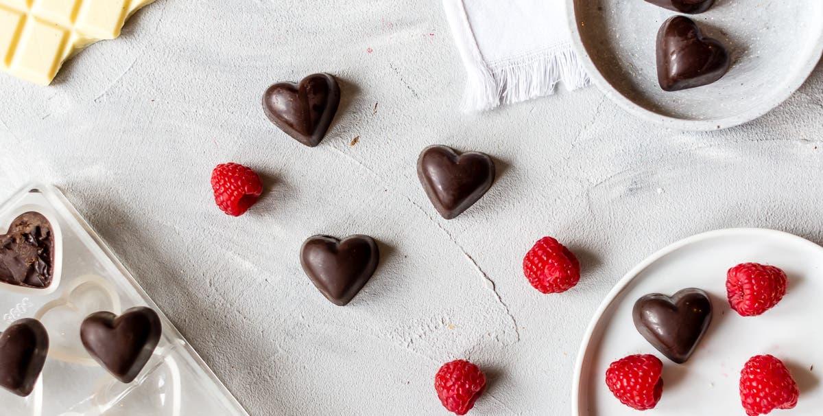 Frische Himbeeren, weiße Schokolade und Schokoladenpralinen in Herzform.