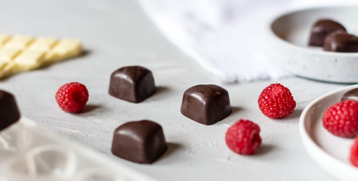 Herzpralinen mit Schokoladenüberzug und frischen Himbeeren.