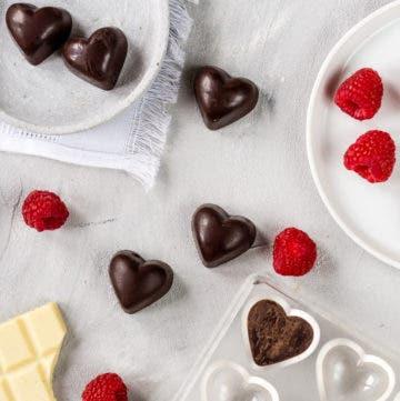 Schokoladenpralinen in Herzform, frische Himbeeren und weiße Schokolade