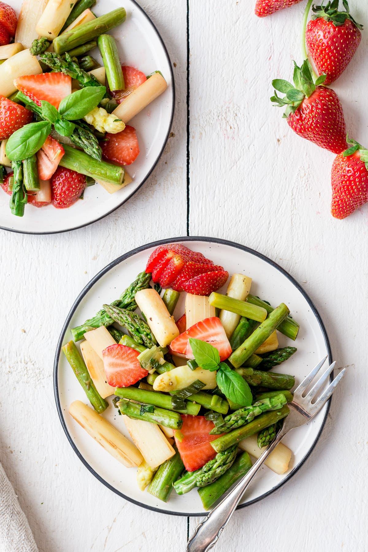 Nahaufnahme von Spargelsalat mit Erdbeeren, Lauchzwiebel und Basilikum