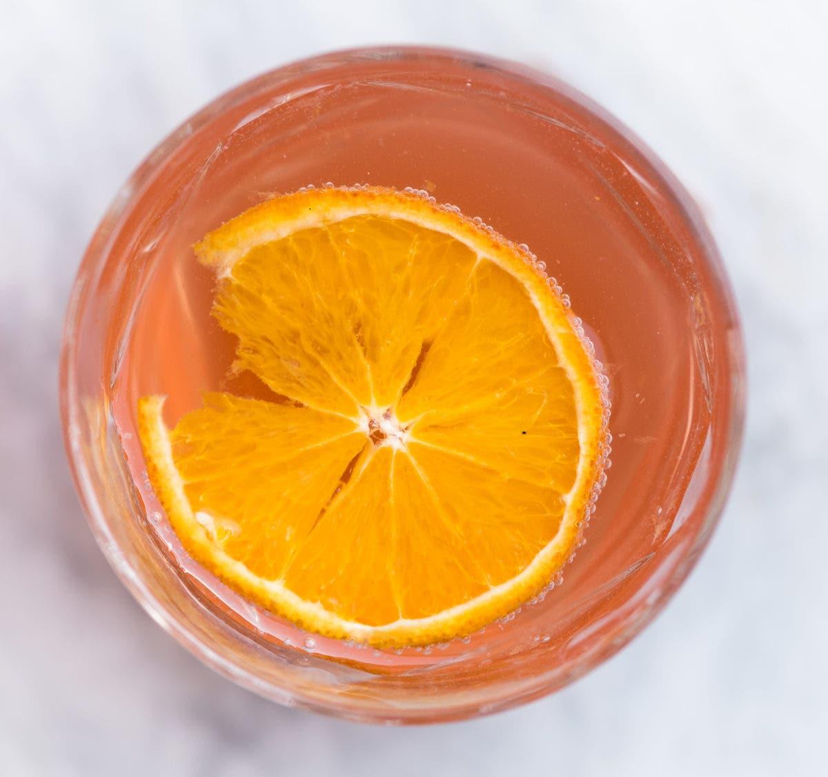 Topshot von Glas mit orangefarbener Limonade und Orangenscheibe darin