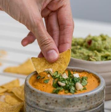 Hand taucht Nacho in Käsedip
