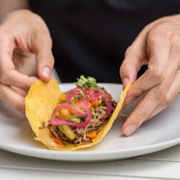 Hand rollt befüllten Taco auf weißem Teller