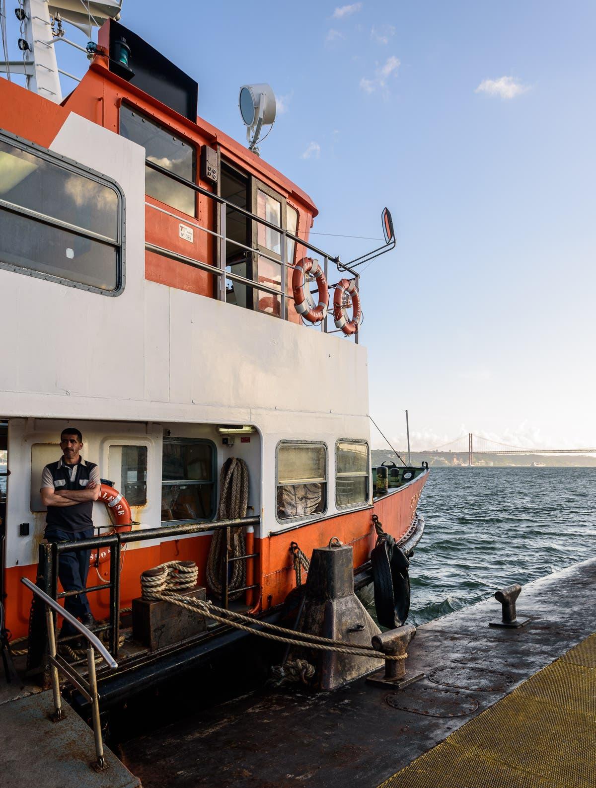 orange, weißes Boot, das an Anlegestelle wartet