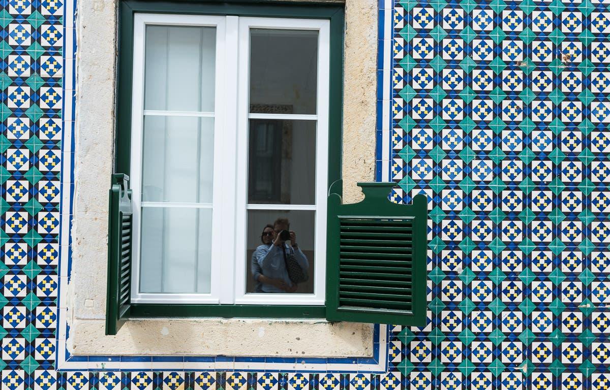 Haussfassade mit grün-blauen Mosaiken und grünen Fensterläden